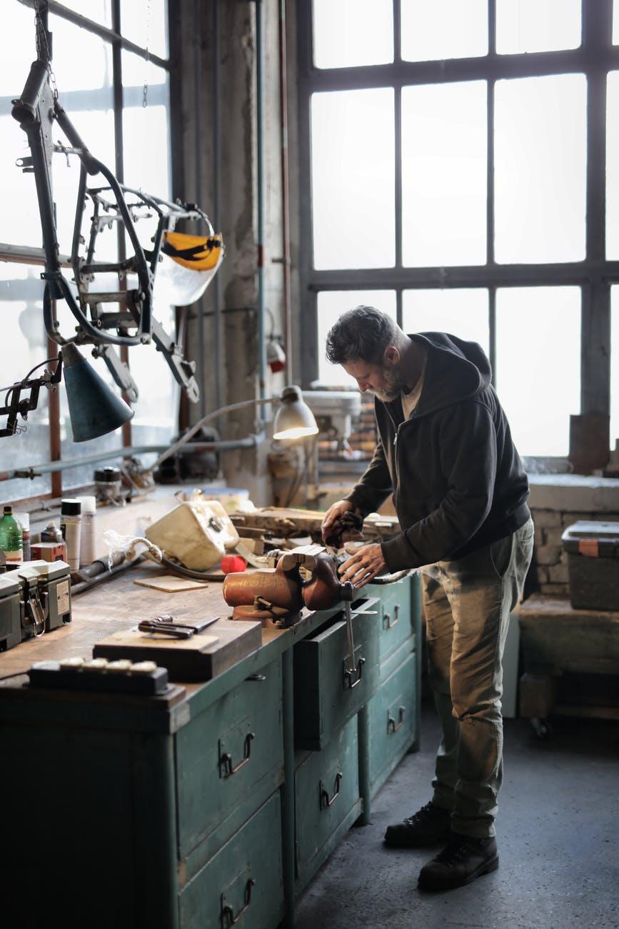 self employed male mechanic working in garage